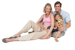 Glückliche junge Familie, die eine Neuheit lächelt an der Kamera erwartet lizenzfreie stockfotos