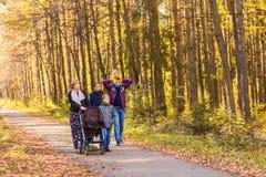 Glückliche junge Familie, die hinunter die Straße draußen in der Herbstnatur geht Lizenzfreies Stockbild