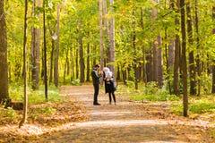 Glückliche junge Familie, die hinunter die Straße draußen in der Herbstnatur geht Lizenzfreie Stockfotos