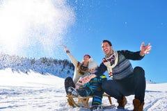 Glückliche junge Familie, die im frischen Schnee am schönen sonnigen Wintertag im Freien in der Natur spielt Lizenzfreie Stockfotos