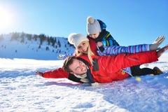 Glückliche junge Familie, die im frischen Schnee am schönen sonnigen Wintertag im Freien in der Natur spielt lizenzfreie stockbilder