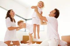 Glückliche junge Familie, die im Schlafzimmer spielt Stockfotografie