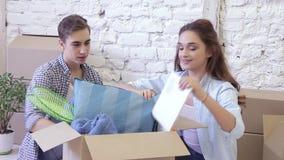 Glückliche junge Familie, die Kästen nachdem dem Bewegen auf ein neues Haus auspackt stock video
