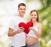 Glückliche junge Familie, die Kind mit großem Herzen erwartet Stockbild