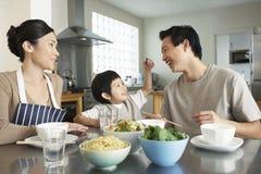 Glückliche junge Familie, die Mahlzeit genießt lizenzfreie stockfotografie