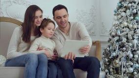Glückliche junge Familie, die selfies auf Sofa mit Tablette nimmt stock footage