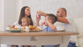 Glückliche junge Familie, die Tee mit Bonbons am Restaurant oder Café oder Haus genießt Stockfoto
