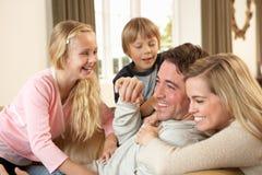 Glückliche junge Familie, die zusammen auf Sofa spielt Lizenzfreies Stockbild