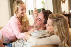 Glückliche junge Familie, die zusammen auf Sofa spielt Stockbild