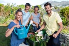 Glückliche junge Familie, die zusammen im Garten arbeitet Stockfotos