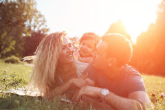 Glückliche junge Familie, die zusammen Zeit draußen in der grünen Natur verbringt Stockbild