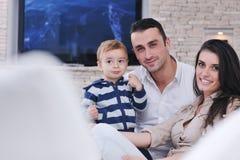 Glückliche junge Familie haben Spaß mit Fernsehapparat im backgrund Stockbild