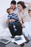 Glückliche junge Familie haben Spaß mit Fernsehapparat im backgrund Lizenzfreie Stockfotos