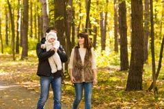 Glückliche junge Familie im Herbstpark draußen an einem sonnigen Tag Mutter, Vater und ihr kleines Baby gehen herein lizenzfreie stockbilder