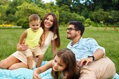 Glückliche junge Familie im Park Eltern und Kinder, die den Spaß, spielend haben stockfoto