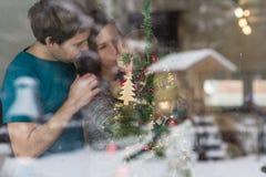 Glückliche junge Familie mit Baby hinter verziertem Weihnachtsbaum an stockbild