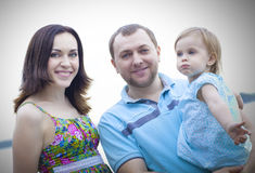 Glückliche junge Familie mit dem Baby, welches die Zeit im Freien verbringt Stockfotografie