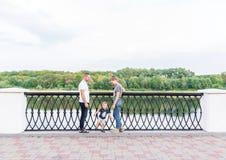 Glückliche junge Familie mit ihrem kleinen Sohn verbringen Zeit zusammen im Stadtpark Lizenzfreie Stockbilder
