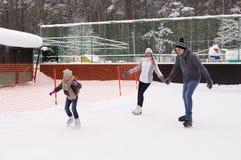 Glückliche junge Familie mit Kinderrochen an der Eisbahn im Freien im Winter Schöne Familie, die herein auf dem Eis geht und spie stockbild