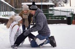 Glückliche junge Familie mit Kinderrochen an der Eisbahn im Freien im Winter Schöne Familie, die herein auf dem Eis geht und spie stockfotos