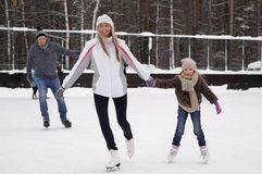 Glückliche junge Familie mit Kinderrochen an der Eisbahn im Freien im Winter Schöne Familie, die herein auf dem Eis geht und spie lizenzfreies stockfoto