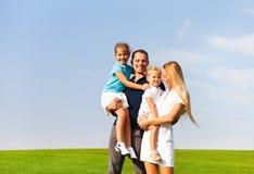 Glückliche junge Familie mit zwei Kindern draußen Stockfoto