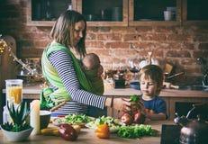 Glückliche junge Familie, schöne Mutter mit zwei Kindern, entzückender Vorschuljunge und Baby im Riemen zusammen kochend in einem stockbilder