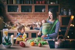 Glückliche junge Familie, schöne Mutter mit zwei Kindern, entzückender Vorschuljunge und Baby im Riemen zusammen kochend in einem stockfotos