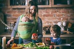 Glückliche junge Familie, schöne Mutter mit zwei Kindern, entzückender Vorschuljunge und Baby im Riemen zusammen kochend in einem lizenzfreies stockbild