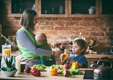 Glückliche junge Familie, schöne Mutter mit zwei Kindern, entzückender Vorschuljunge und Baby im Riemen zusammen kochend in einem stockbild