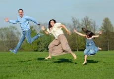 Glückliche junge Familie. Spiele in der Natur Stockfotografie
