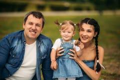 Glückliche junge Familie, welche die Zeit im Freien an einem Sommertag verbringt lizenzfreie stockbilder