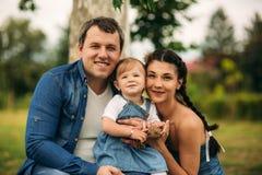 Glückliche junge Familie, welche die Zeit im Freien an einem Sommertag verbringt stockfotos