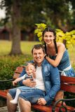 Glückliche junge Familie, welche die Zeit im Freien an einem Sommertag verbringt stockbild
