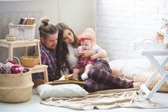 Glückliche junge Familienmutter, -vater und -tochter, die zu Hause auf Teppich spielt Lizenzfreies Stockfoto