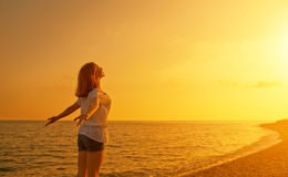 Glückliche junge Frau öffnen ihre Arme zum Himmel und zum Meer bei Sonnenuntergang Lizenzfreie Stockbilder
