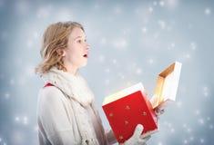 Glückliche junge Frau überglücklich, nachdem ein großes rotes Geschenk geöffnet worden ist Stockbild