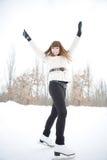 Glückliche junge Frau auf dem Eislaufenring Stockbild