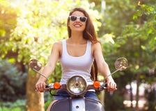 Glückliche junge Frau auf einem Roller auf der Straße und dem Lächeln Lizenzfreie Stockfotografie