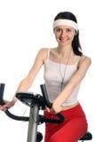 Glückliche junge Frau auf einem Trainingsfahrrad Lizenzfreies Stockbild