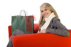 Glückliche junge Frau auf roter Couch Stockbild