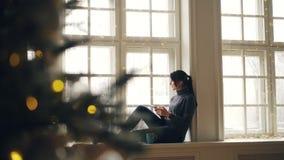 Glückliche junge Frau benutzt den Smartphone, der auf Fensterbrett am Weihnachtstag zu Hause entspannend und genießend modern sit stock video