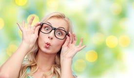 Glückliche junge Frau in den Gläsern, die Fischgesicht machen Stockfotografie