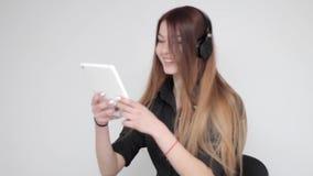 Glückliche junge Frau in den Kopfhörertänzen hört Musik und macht Foto auf Tablette stock video footage
