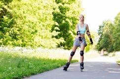 Glückliche junge Frau in den Rollerblades, die draußen reiten Stockbild