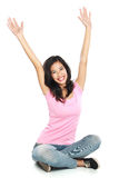 Glückliche junge Frau in der Freizeitkleidung, die mit angehobenem Arme smilin sitzt Stockfoto