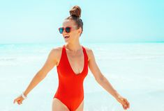Glückliche junge Frau in der roten Badebekleidung auf dem Strand, der Spaßzeit hat stockfoto