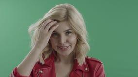 Glückliche junge Frau in der roten Jacke gegen grünen Schirm stock footage