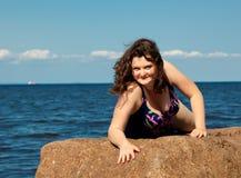Glückliche junge Frau in der Schwimmenreihe, die auf Felsen legt.  Seeufer lizenzfreie stockfotografie