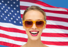 Glückliche junge Frau in der Sonnenbrille über amerikanischer Flagge Lizenzfreies Stockfoto